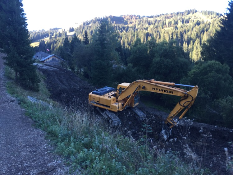 A digger hopefully getting rid of the flat spot on the Bleuet run, Les Gets