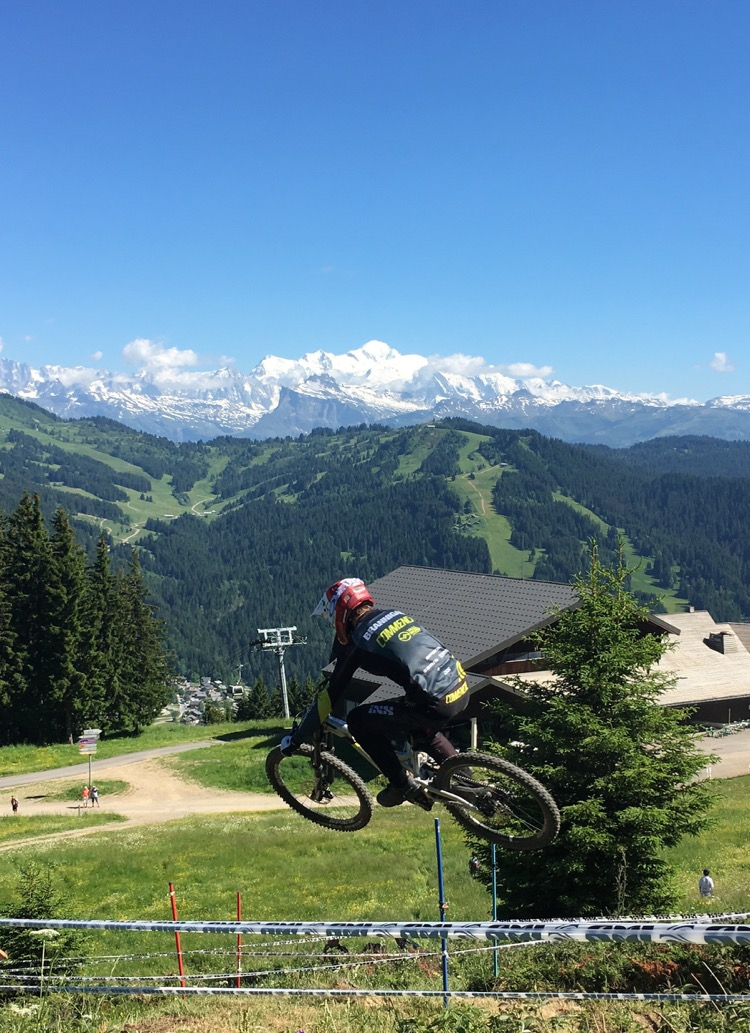 George Brannigan motoring down the Crankworx Les Gets 2017 downhill course and barely missing a padded tree in the landing. Mont Chery lift station and Mont Blanc in the background.