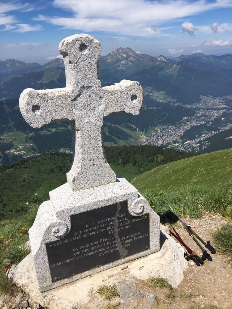 The summit cross of Pointe de Ressachaux with Morzine below and Roc d'Enfer beyond.