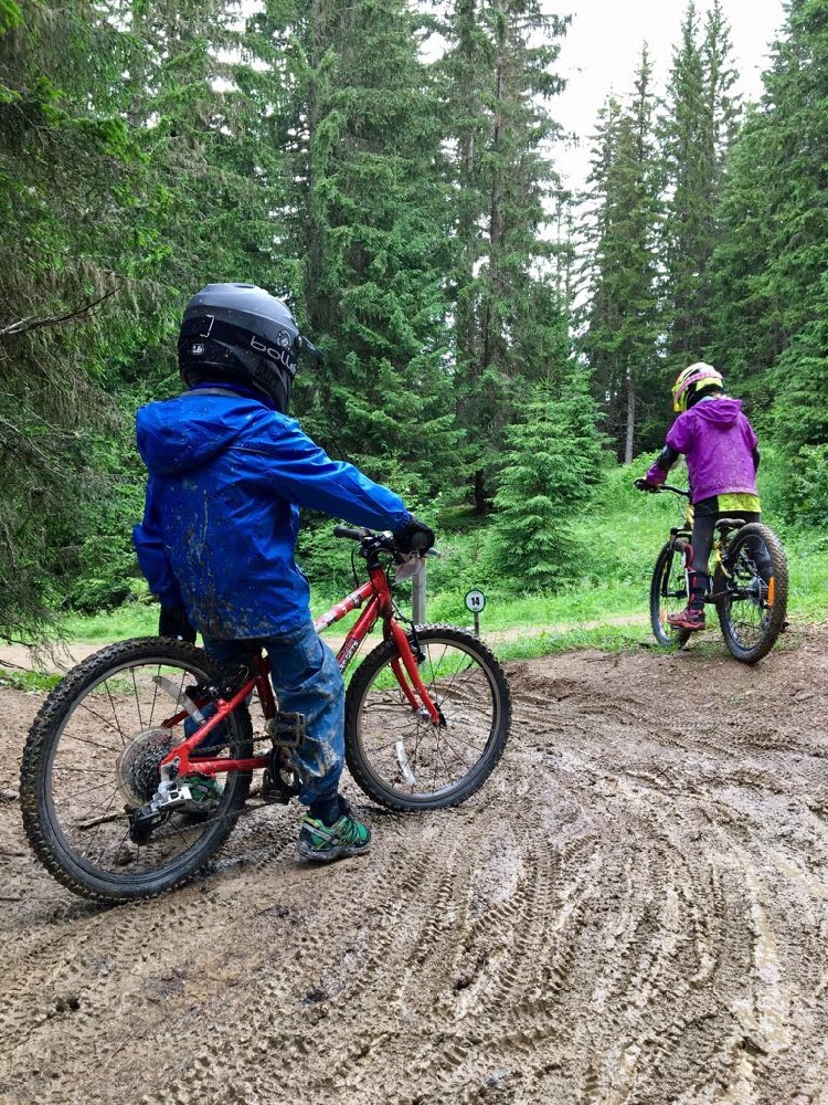 child in blue waterproofs on red Islabike and young girl on mountain bike on muddy ground. Family biking Super Morzine.