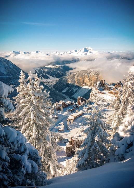 Looking through the snow covered trees of Avoriaz, past the cliffs on to Morzine in the valley below. UpStix images.